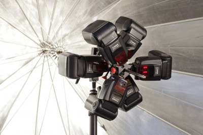 Two Triple Threats holding six speedlights inside a parabolic umbrella