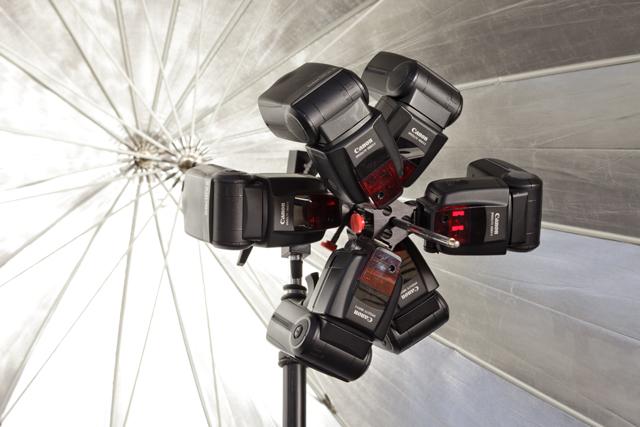 Two Triple Threats holding six speedlights inside a parabolic umbrella