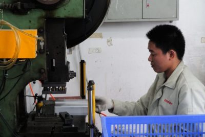 A Godox worker making the metal shells of studio flash heads